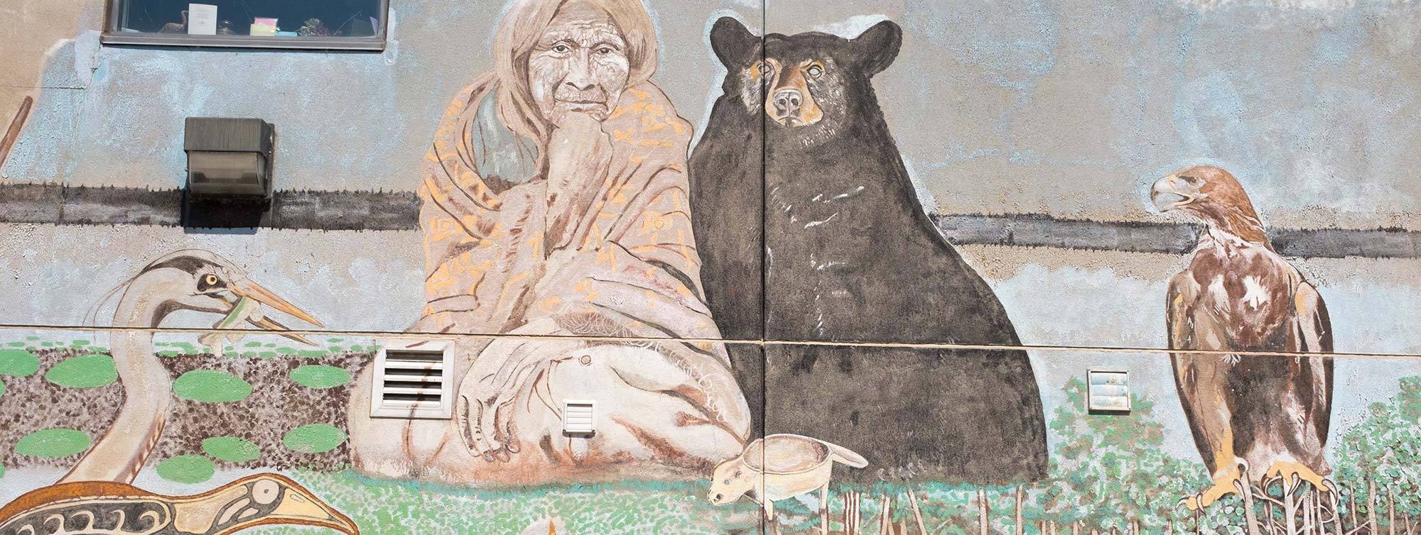 Indigenous art wall mural in Rama, Ontario showing an Elder, black bear, and an eagle