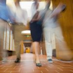 Low angle view of a group of blurred people walking through open doors